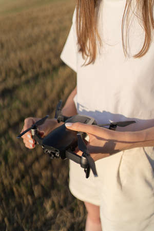 A beautiful girl folds a drone and puts it on her hand. Technological gadget in womens hands at sunset against the sky Standard-Bild