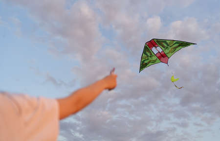 Kite is flying. Hand holds flying kite at sunset, amid beautiful clouds