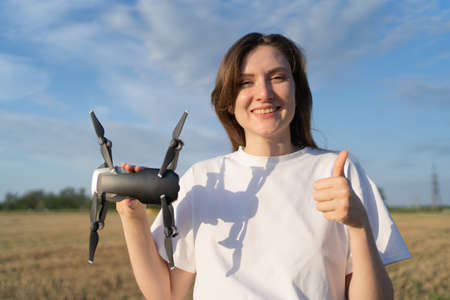 Permission to fly a drone. The operator of the quadcopter shows the like and the drone. Smiling girl with a drone in her hand