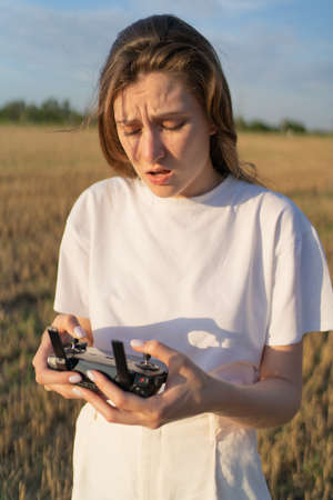 Drone control. Female pilot tries to control quadcopter in flight