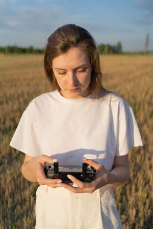 A beautiful young woman in a field controls a drone in flight. Control the drone through a remote control