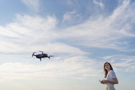 A woman controls the flight of a drone. The quadcopter hovered in the air, the female drone pilot looks at the drone