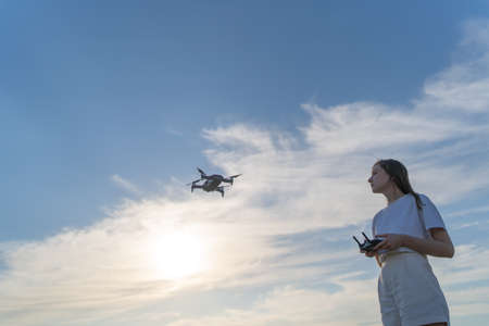 A woman learns to control a drone. Training to fly on a quadcopter in a safe place Standard-Bild