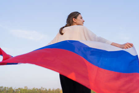 Russian flag. Back view of a woman walking with a flag in nature. Symbol of independence and patriotism of the Russian Federation Standard-Bild