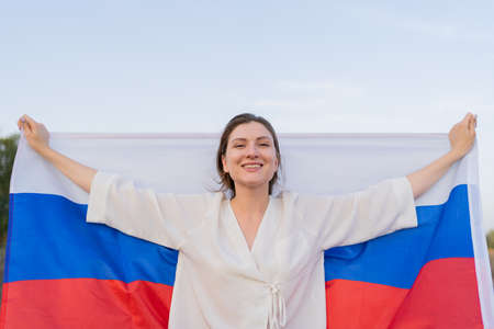 Beautiful Russian woman with Russian flag in her hands, portrait, front view. The woman raises the flag behind her back, smiles and looks at the camera Standard-Bild