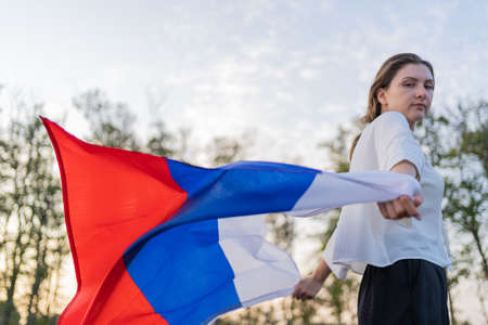 A woman runs with the Russian flag in her hands. The symbol of Russia waving beautifully in the hands of a woman