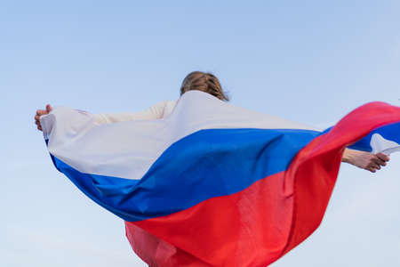 A happy Russian woman whirls with the Russian flag. Independence Day of the Russian Federation