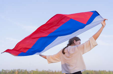 The flag of Russia beautifully waving behind the back of a woman. Russias Independence Day