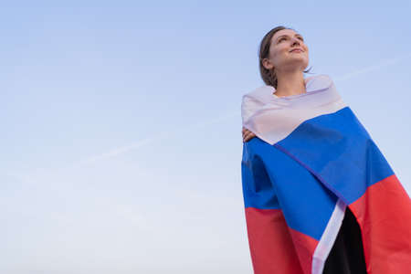 Patriot woman. A beautiful Russian woman with the flag of the Russian Federation looks to the future against the bright sky at sunset. A place for your text Standard-Bild