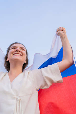 Woman with the Russian flag celebrating the victory in the competition. Excited Russian cute woman against the sky