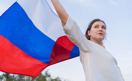 The symbol of Russia - flag in the hands of a woman. Independence and patriotism