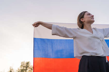 Portrait of a beautiful Russian woman with a flag at sunset against the sky Standard-Bild