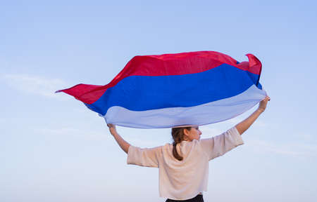 A woman with the flag of Russia runs in nature. Happiness and patriotism, waving flag of the Russian Federation