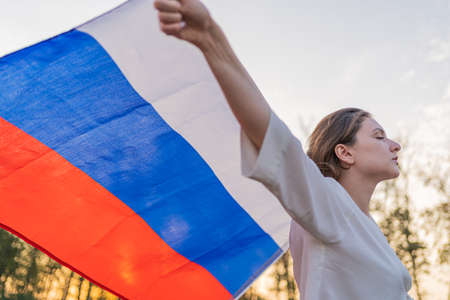 Beautiful Russian woman with a flag against the sunset Standard-Bild