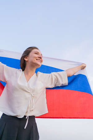 Woman with flag of the Russian Federation against the blue sky. Russias Independence Day