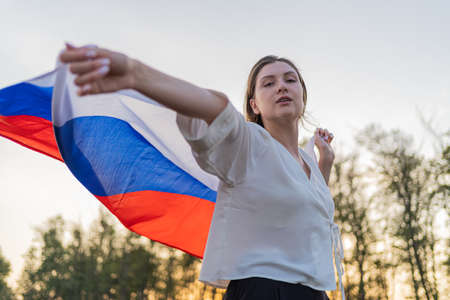 The face of a beautiful woman with a Russian flag in her hands. Pretty woman walks with a flag behind her back against the sunset sky