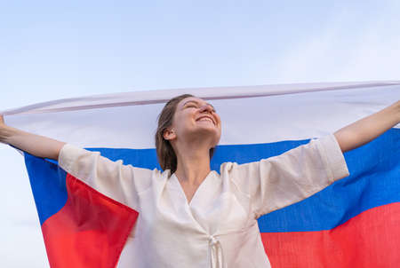 The flag of Russia behind the young beautiful woman