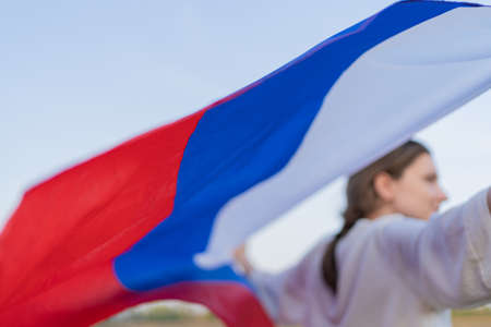 The symbol of Russia is a tricolor flag: white, blue and red. A young woman holds a flag behind her back in the wind