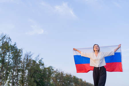 Portrait of a Russian beautiful woman with the national flag. Symbol of the Russian Federation