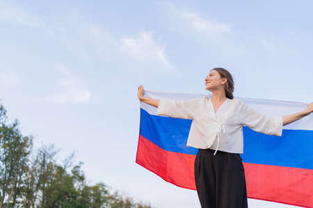 Person with the flag of Russia stands and washes into the distance. A woman patriot looks happily to the future