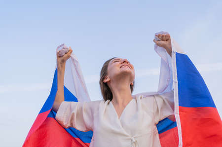 A Patriotic excited woman with a Russian flag celebrates her victory. Happiness and independence