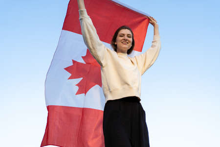 A beautiful young woman with the flag of Canada goes against the background of the forest. Canadian patriot smiles and looks into the camera Standard-Bild
