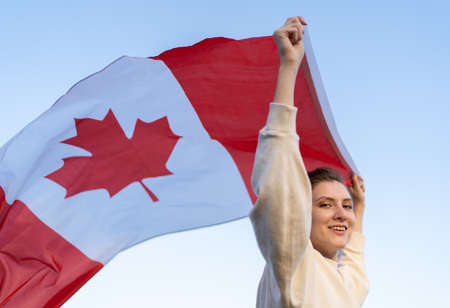A woman carries the Canadian flag in her hands, it waving in the wind. Immigrant in a free country with a national symbol Standard-Bild