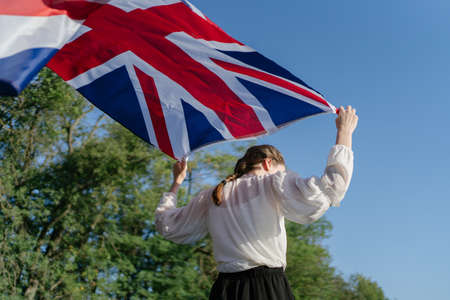 A British person carries the national flag in her hands. The symbol of Great Britain waving on the wind