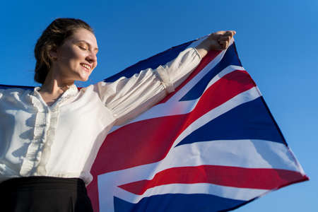 Patriot with the national flag of Great Britain. Independent woman smiles and rejoices