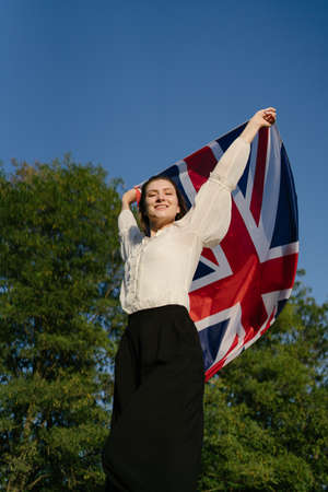 An English woman with the British flag dances in nature, success and happiness Standard-Bild
