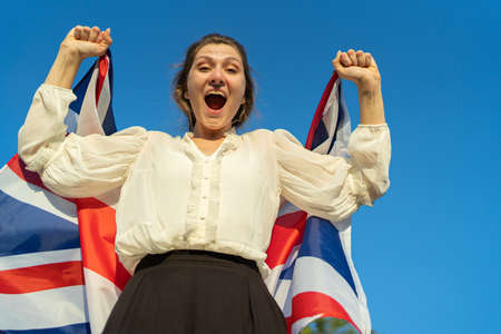 Winner in the UK. Woman with British flag rejoices in success and shouts at the camera