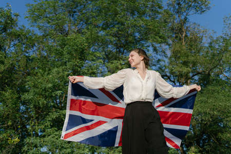 Happy young Englishwoman with the British flag. Independent woman patriot Standard-Bild