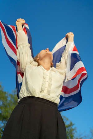 Reaching a goal and success in the UK. Student with English flag in hands Standard-Bild