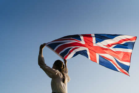 A woman runs with the flag of Great Britain against a clear sky. Patriotism of citizen of England