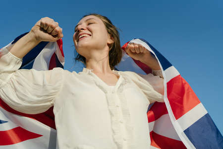 Triumph and glory in the Great Britain. Woman with English flag in hands Standard-Bild