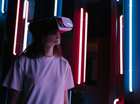 VR experience. Young woman in neon light in a virtual reality headset