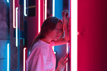 A beautiful young woman in a strong red light of neon lamps. Fashionable nightlife, futurism and ultraviolet