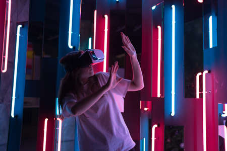 A young woman in headset is explore VR. Neon light. A joyful new experience in entertainment
