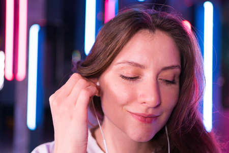 A woman inserts headphones into her ears and dances in the neon. Happy emotional beauty listens to music with headphones Foto de archivo