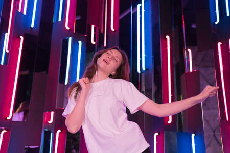 Celebrate and dance against neon. Beautiful woman in white T-shirt enjoys dancing in headphones
