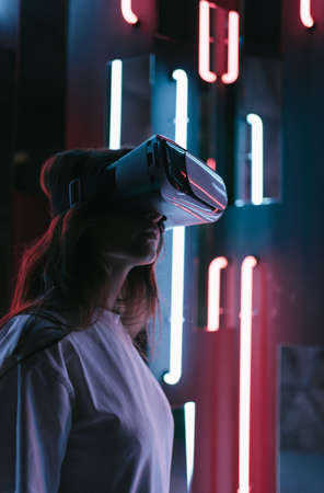A young woman is immersed in virtual reality. Modern technology in entertainment