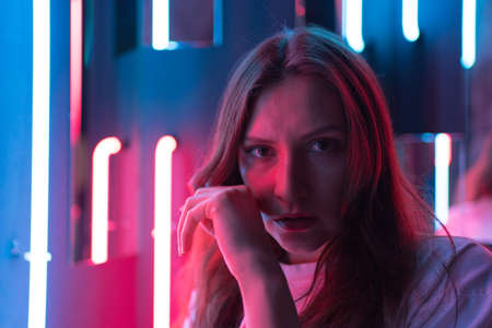 Portrait in the light of a neon lamp. Beautiful woman statically looks into the camera, close-up