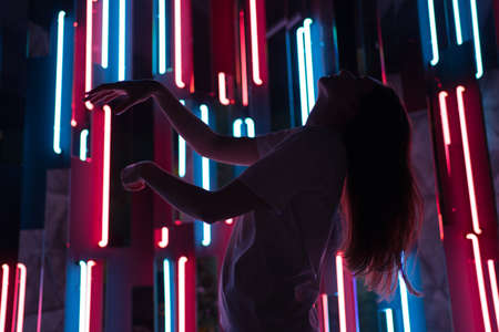 Slender woman dances relaxed in the background of neon. The silhouette of a dancer in a beautiful light of different colors Imagens