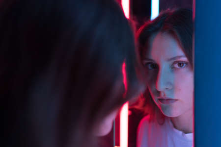 A female portrait in the reflection of a neon mirror. Beautiful woman look at the camera