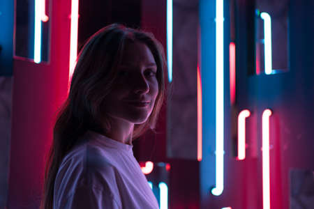 Womans smile in the light of neon. Glamorous beauty looks into the camera Фото со стока