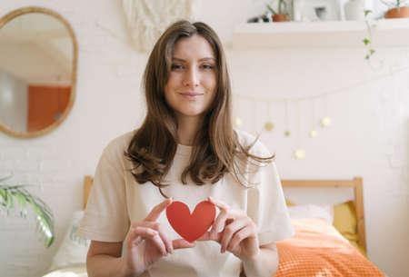A romantic beautiful woman with a red paper heart in her hands smiles and looks into the camera. Symbol of Valentines Day