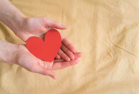 Beautiful paper heart-valentine in open hands against the background of yellow fabric. February 14