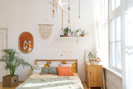 A cozy room in the sunlight. Beautiful bed in a modern interior Imagens