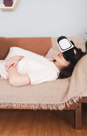 A woman rests on the couch in a virtual reality headset. Watch movies in cyberspace. Scandinavian interior