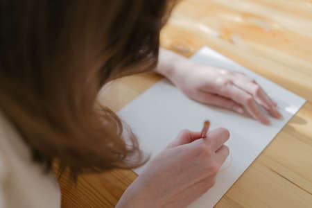 The artist drawing a picture in a cozy interior with a yellow pencil. Creativity and inspiration at work. Home hobbies